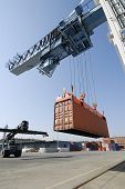 stock photo of container ship  - crane lowering container to waiting forklift truck - JPG