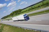 clean blue-white truck speeding on highway, no trademarks