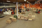 interior of warehouse with moving people, packages and parcels