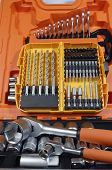 professional tool-box with adjustable keys and box of drills in background
