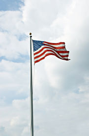 stock photo of waving american flag  - American flag waving from flagpole with cloudscape - JPG