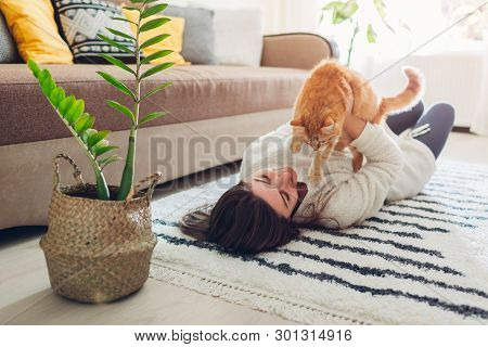 poster of Young Woman Playing With Cat On Carpet At Home. Master Lying On Floor With Her Pet