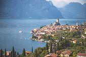 Idyllic Coastline Scenery In Italy: Blue Water And A Cute Village At Lago Di Garda, Malcesine poster