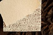 Background image with parchment paper over a page with faux handwriting (non legible) and brown suede fabric.