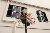 Street Lamp With Flower Pots On House Facade In Hamilton, Bermuda. Potted Flowers On Lighting Column poster