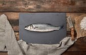 Fresh Whole Sea Bass Fish On Black Board , Top View poster
