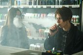 Vape Teenagers. Young  Handsome Guy And Young Cute Girl In Sunglasses Smoke An Electronic Cigarettes poster