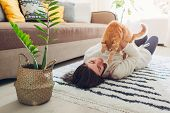 Young Woman Playing With Cat On Carpet At Home. Master Lying On Floor With Her Pet poster