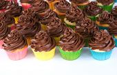 lots of chocolate frosted cupcakes in rainbow wrappers