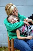 stock photo of tickle  - Mother tickles daughter and child is laughing - JPG