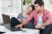 stock photo of concubine  - Couple relaxing at home in front of their laptop - JPG