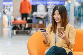 Asian Woman Using Credit Card With Mobile Phone For Online Shopping In Department Store Over The Clo poster
