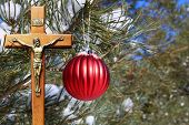 Red Christmas Ornament Hanging Outside On An Evergreen Tree With Wooden Crucifix With Gold Body Of J poster