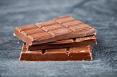 Milk chocolate bar pieces closeup. Sweet food photo concept. Chunks of chocolate stacked on grey bac poster