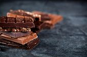 Chunks of broken chocolate stacked on black board. Chocolate bars pieces stack on black background.  poster
