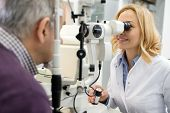 Sympathetic female eye doctor looks at patient eyes using apparatus in eyes clinic  poster