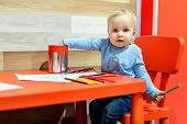 Cute Little Caucasian Blond Toddler Boy Sitting At Table And Drawing At Children Area At Retail Clot poster