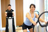 stock photo of vibration plate  - Group of two men and one woman on a vibration massage plate in a gym