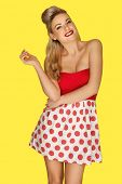 Glamorous blonde retro fashion model in a red polka dot miniskirt with vivid red lipstick and an old