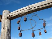 picture of windchime  - Hanging antique heart windchime on yard fence with azur sky background - JPG