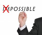 Businessman in suit drawing text of the word impossible with red mark through part of the word makin