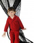 A beautiful preschooler in red pajamas, standing befor the lacy black curtain that she's twisted.  On a white background.
