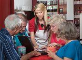 Helpful Waitress With Seniors On Laptop