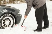 foto of snow shovel  - Man digging car out of the snow - JPG