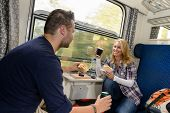 Couple enjoying sandwiches traveling with train smiling woman man vacation