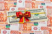 Folded Dollar Bills Laying Over Rouble Background