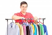 A smiling guy posing on a hang rail full of clothes isolated on white background