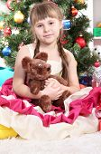 Beautiful little girl in holiday dress with toy in hands in festively decorated room