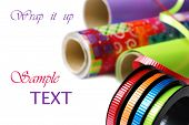 Brightly colored curling ribbon on spool with rolls of wrapping paper on white background with copy