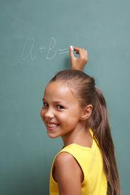 stock photo of little school girl  - Cheerful school girl writing on chalk board - JPG