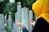stock photo of sufi  - veiled woman praying in front of the old tombstones - JPG