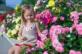 Portrait Of Cute Little Girl Near The Flowers In The Yard Of Her House