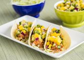 stock photo of mango  - Corn tortillas filled with shredded lettuce shredded barbecue chicken and topped with mango pineapple salsa - JPG