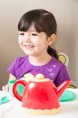 Girl Laughing As She Plays Tea Party
