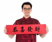 Asian man with Chinese traditional cheongsam or tang suit holding couplet, the Chinese word means co