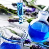 closeup of a pipette and a flask with flower essence and a pile of lavender flowers in the background