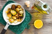 stock photo of sauteed  - Delicious sauteed brussels sprouts with olive oil and fresh lemon for a tangy zesty flavour in a saucepan on a rustic tabletop in a country kitchen overhead view - JPG