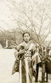 JAPAN - CIRCA 1940-1950s: An antique photo shows a woman in kimono standing by Sakura tree