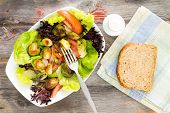 stock photo of sauteed  - Delicious fresh leafy green mixed salad with diced and sauteed brussels sprouts served on a rustic wooden table with a slice of brown bread for a healthy lunch overhead view - JPG