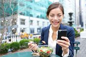 Постер, плакат: Young business woman eating salad on lunch break in City Park living healthy lifestyle working on sm