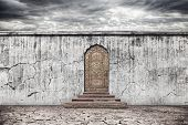 pic of barricade  - Grunge grey wall and vintage door with oriental ornament on dry earth with cracks at dramatic sky background - JPG