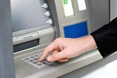 Man Enters A Pin Code to Withdraw Money From An Atm