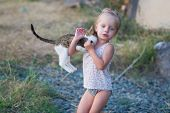 Little Girl Playing With Kitten Outdoors