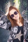 Young happy girl wearing military uniform and sunglasses