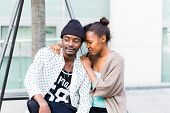 African man sitting with girlfriend in the city