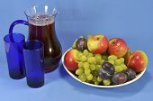 stock photo of fruit platter  - Pitcher with fruit juice two glasses and fruits on a platter on a blue background - JPG
